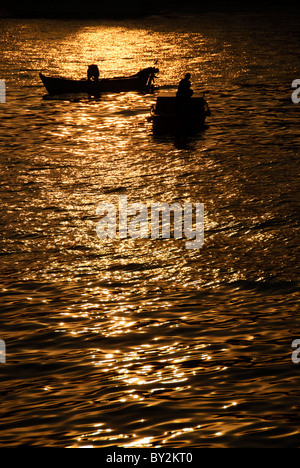 Two small fishing boats are silhouetted against the reflection of the setting sun on the Bosphorus in Istanbul, - Stock Photo