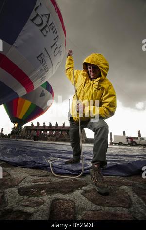 a man pulls a balloon while it's inflated in the Centro Ceremonial Otomi, Estado de Mexico, Mexico. - Stock Photo