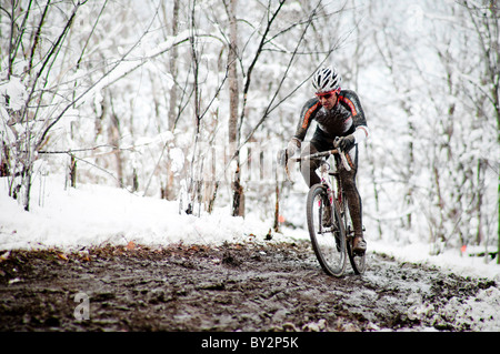 A cyclists races in the mud and snow at a Cyclocross race in Boulder, CO. - Stock Photo