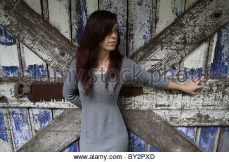 A pretty woman in her 20s with long dark hair standing next to a barn. - Stock Photo