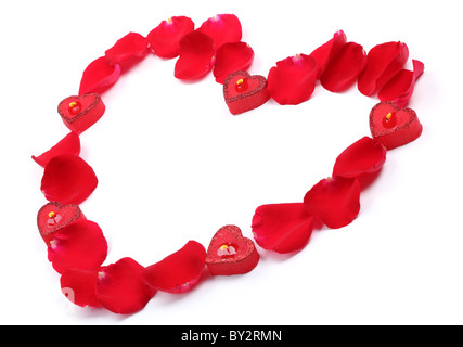 Rose petals and candles forming heart shape on white background. - Stock Photo