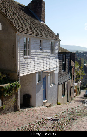 Steep cobblestone street known as Keere Street. Lewes. East Sussex. England. House with white painted tile clad - Stock Photo