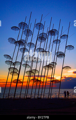 Greece, Thessaloniki. Two young ladies enjoying the sunset under a structure, called 'The Umbrellas' by George Zoggolopoulos. - Stock Photo