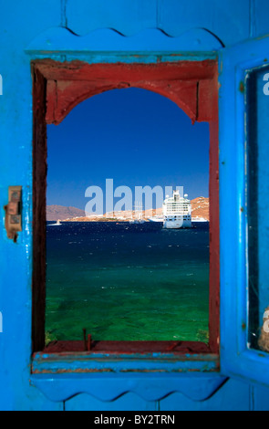 A view through the window from one of the old houses right by the sea in the Hora of Myconos, Greece - Stock Photo