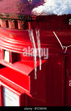 Traditional red Royal Mail post box with icicles - Stock Photo