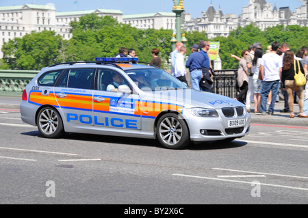 Street scene uniformed officers in Metropolitan Police patrol car driving across Westminster Bridge with group of - Stock Photo