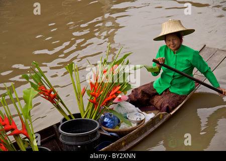 Flower seller wearing a green jacket selling bunches of Heliconia caribaea from a boat on the canal at Amphawa Floating - Stock Photo