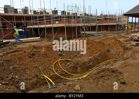Trench in the ground around a new housing development under construction England UK. - Stock Photo