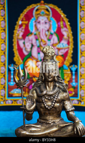 Lord Shiva, Indian Deity statue in front of Ganesha wall hanging. India - Stock Photo