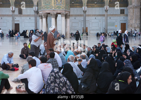 Visitors listen attentively to a holy man in the courtyard of the Great Umayyad Mosque, Damascus, Syria - Stock Photo