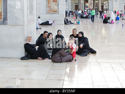Syrian family relaxing in Great Umayyad Mosque, Damascus, Syria - Stock Photo