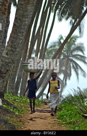 Girls carrying baskets walking along a coastal path in Sassandra, Ivory Coast, West Africa - Stock Photo