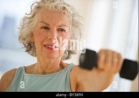 USA, New Jersey, Jersey City, Senior woman using hand weights at gym - Stock Photo