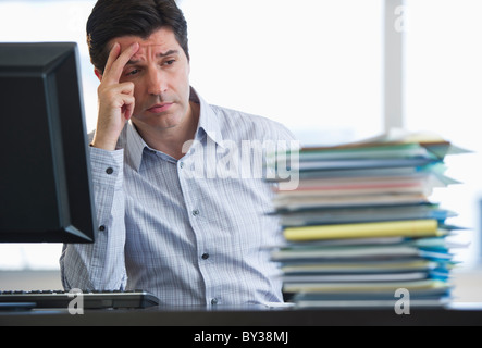 USA, New Jersey, Jersey City, Businessman staring at stacked paperwork on desk