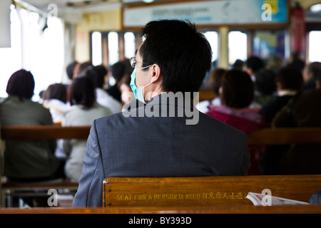 Commuter with face mask on Star Ferry crossing Victoria Harbour between Kowloon and Hong Kong Island. JMH4142 - Stock Photo