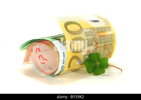Euro notes with four-leaf clover on white background - Stock Photo