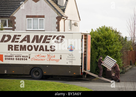 Men carrying furniture into a removal van in the street outside a house for home removals. North Wales, UK, Britain. - Stock Photo