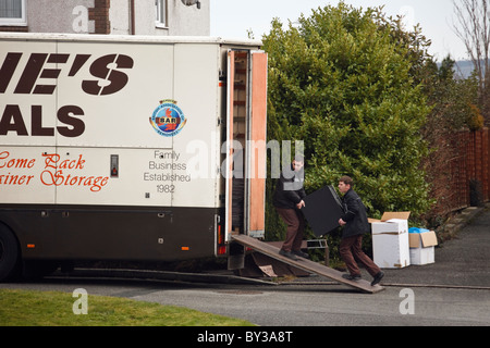 North Wales, UK, Europe. Men carrying furniture into a removal van in the street outside a house for home removals - Stock Photo