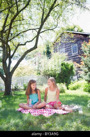 USA, New York, Two girls (10-11, 10-11) sitting on blanket in backyard - Stock Photo
