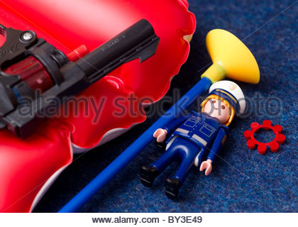 Childrens toys - cap gun with plastic tipped arrow, caps and a toy figurine - Stock Photo