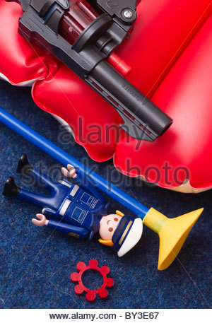 Childrens toys - toy cap gun with small figurine and a plastic tipped arrow - Stock Photo