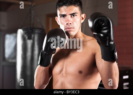 USA, Seattle, Portrait of young man in gym wearing boxing gloves - Stock Photo