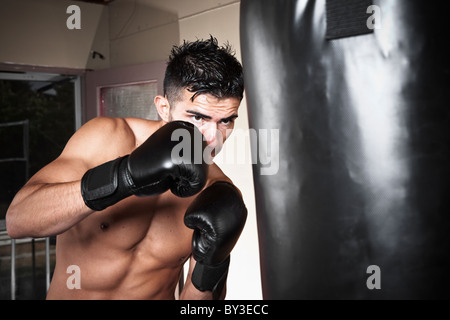 USA, Seattle, Portrait of young man boxing in gym - Stock Photo