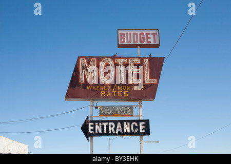 USA, Arizona, Winslow, Old-fashioned motel sign against blue sky - Stock Photo