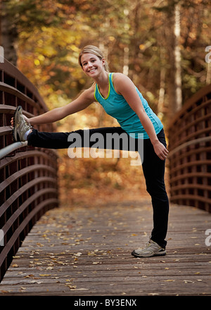 Young woman stretching on bridge - Stock Photo