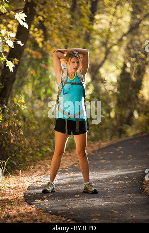 USA, Utah, young woman standing on footpath in forest - Stock Photo