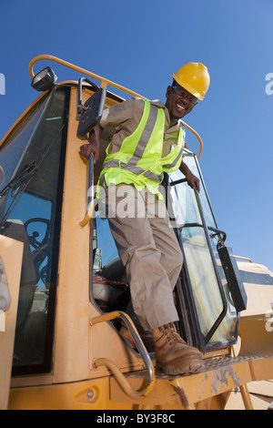 Portrait of construction worker on mechanical digger - Stock Photo
