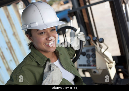 Portrait of female construction worker driving mechanical digger - Stock Photo