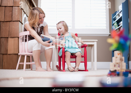 USA, Utah, small girl (2-3) with nanny reading book - Stock Photo