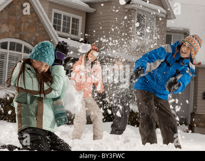 USA, Utah, Provo, Boys (10-11, 12-13) and girls (10-11, 16-17) having snow ball fight in front of house - Stock Photo