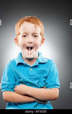 Portrait of smiling redhead boy (4-5) wearing blue polo shirt and making face, studio shot - Stock Photo