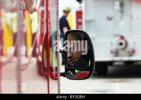 A firefighter reflection in the fire truck vehicle rear view side mirror and a firefighter in the background