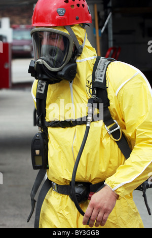 A firefighter in a secured the hazmat suit walking at a chemical haz mat spill incident - Stock Photo