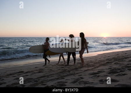 Surfers walking along the beach at sunset - Stock Photo