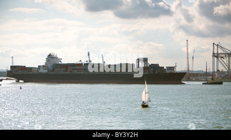 Sailing in the solent,Southampton waters, in the shadow of a berthing container ship 'Maersk Sarnia'. - Stock Photo
