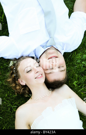 View from above of happy newlyweds lying on green grass and touching each other's faces - Stock Photo
