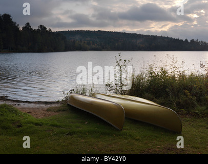 Two canoe on a shore of The Lake of Two Rivers at dawn tranquil fall scenery. Algonquin Provincial Park, Ontario, - Stock Photo