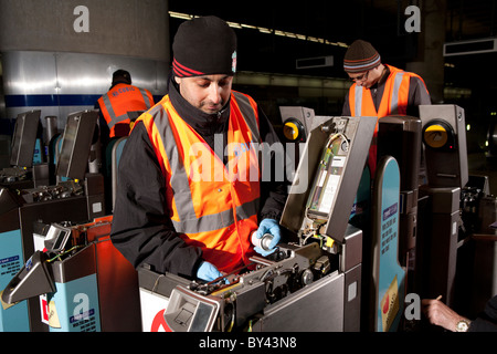engineers work at night maintaining ticket barriers at canary wharf station on london underground - Stock Photo