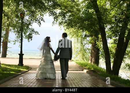 Portrait of bride and groom holding each other by hand outside - Stock Photo