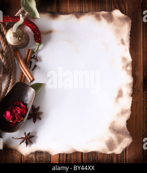 Image of old paper with spices on a wooden surface - Stock Photo