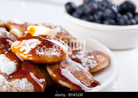 Dutch mini pancakes, or poffertjes, with butter, syrup and powdered sugar. Fresh blueberries out of focus in the - Stock Photo