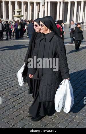 nuns walking in saint peter's square with shopping bags shoppers  vatican city san pietro Rome Italy - Stock Photo