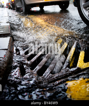 Rain water flowing in to a grate at the side of a road in Birmingham, UK - Stock Photo