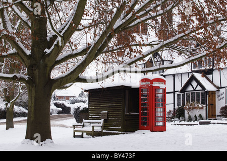 Red telephone box with snow on English village green - Stock Photo