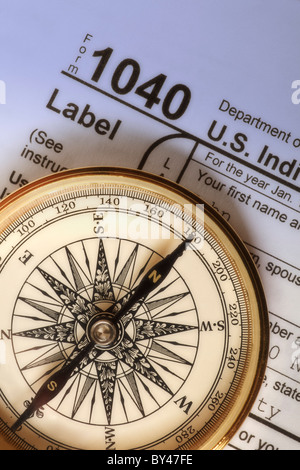 Compass on a Federal Income Tax 1040 form illustrating the concept of income tax preparation and guidance - Stock Photo