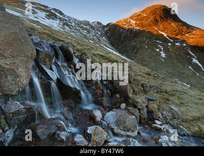 Browney Gill waterfall and first light on Great Knott near Crinkle Crags in the English Lake District - Stock Photo